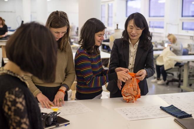 Professor Ryoko Matsuo guides ASN student Flavia Salvador in a 'furoshiki' cloth wrapping workshop.